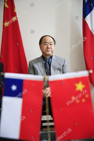 Chinese Writer and 2012 Nobel Prize Winner in Literature Mo Yan Sits Next to Chinese and Chilean National Flags During a Signing Ceremony at the Embassy of Chile in Beijing China 31 May 2016 Mo Signed an Agreement with Ramirez During the Ceremony to Adapt His Novel 'Life and Death Are Wearing Me Out' Into a Spanish Stage Play China Beijing