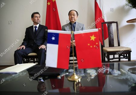 Chinese Writer and 2012 Nobel Prize Winner in Literature Mo Yan (r) and Director of the Chile-china Culture Institute Juan Carlos Ramirez (l) Sit Next to Chinese and Chilean National Flags During a Signing Ceremony at the Embassy of Chile in Beijing China 31 May 2016 Mo Signed an Agreement with Ramirez During the Ceremony to Adapt His Novel 'Life and Death Are Wearing Me Out' Into a Spanish Stage Play China Beijing