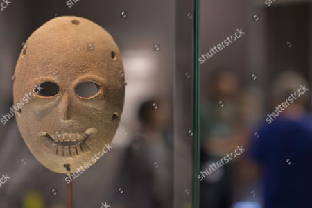 A Limestone Mask From the Neolithic Period (ca 9 000 Years Ago) on Display in the Israel Museum in Jerusalem 05 March 2014 As Workers Install Eleven Additional Ancient Stone Masks Such As This One Called the Dayan Mask For an Exhibition Called 'Face to Face ' the Masks Part of a Collection of Twelve Are the Oldest in the World and Were All Discovered in a Small Area in the Ancient Land of Israel From Outside Jerusalem to the Dead Sea Area This Mask was the Property of Moshe Dayan a Former Israeli Defense Minister who was an Avid Archaeologist and is Said to Have Looted Many of Israel's Archaeological Sites to Make His Enormous Collection of Artifacts Many of Which Now Belong to the State This is One of Two Such Stone Masks in the Museum's Permanent Collection Israel Jerusalem