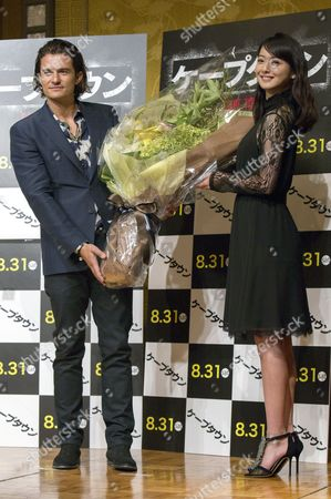 British Actor and Cast Member Orlando Bloom (l) Receives Flowers From Japanese Talent Actress Nozomi Sasaki (r) During a Press Conference For the Movie 'Zulu' (cape Town) in Tokyo Japan 27 August 2014 the Movie Thriller Directed by French Film Director Jerome Salle Will Be Released in Theaters All Across Japan on 30 August Japan Tokyo