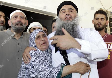 Radical Islamist Cleric Omar Mahmoud Othman (r) Also Known As Abu Qatada is Hugged by His Mother Accompanied Also by His Father (l) Upon Arrival at His Home After a Court Acquitted Him of Terrorism-related Charges in Amman Jordan 24 September 2014 Jordanian Military's State Security Court on 24 September Acquitted Abu Qatada of Terrorism-related Charges Abu Qatada's Case Marks the Third Time a High-profile Radical Cleric Has Been Released by Jordanian Authorities Over the Past Three Months Jordan Amman