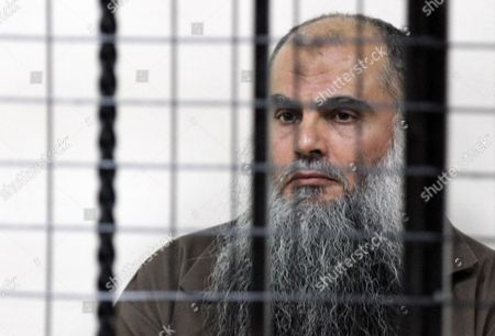 Stock Photo of Radical Islamist Cleric Omar Mahmoud Othman Also Known As Abu Qatada Stands Behind Bars at the Jordanian State Security Court in Amman Jordan 24 September 2014 the Jordanian Court on 24 September Acquitted Radical Cleric Abu Qatada of Terrorism-related Charges the Presiding Judge of the State Security Court Said in a Televized Session That There was Insufficient Evidence That Abu Qatada 53 was Involved in a 2000 Plan Against Tourists Known As the 'Millennium Bombings' Plot Jordan Amman