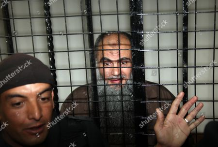 Stock Picture of Radical Islamist Cleric Omar Mahmoud Othman (c) Also Known As Abu Qatada Stands Behind Bars at the Jordanian State Security Court in Amman Jordan 24 September 2014 Others Are not Identified the Jordanian Court on 24 September Acquitted Radical Cleric Abu Qatada of Terrorism-related Charges the Presiding Judge of the State Security Court Said in a Televized Session That There was Insufficient Evidence That Abu Qatada 53 was Involved in a 2000 Plan Against Tourists Known As the 'Millennium Bombings' Plot Jordan Amman