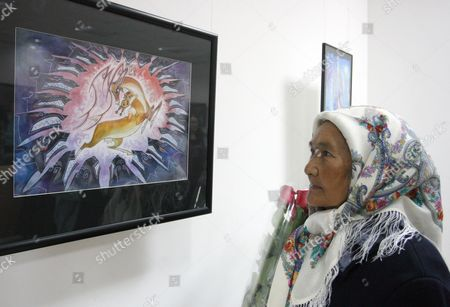 Stock Image of An Elderly Kyrgyz Woman Looks at a Graphic Artwork by Artist Djum at the Exhibition 'Tribe of Wolves' in an Art Gallery in Bishkek Kyrgyzstan 01 November 2013 the Exhibition Focusses on the Life and Culture of Nomadic People Kyrgyzstan Bishkek