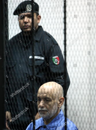 Former Libyan Prime Minister Baghdadi Al-mahmoudi Looks on As He Sits Behind Bars During His Trial in Tripoli Libya 18 February 2014 Al-mahmoudi Faces Charges of Involvement in Crimes Under the Gaddafi Rule Which was Toppled in 2011 He Served As Prime Minister From 2006 Until August 2011 when He Fled to Tunisia After Insurgents Seized Control of Tripoli Virtually Ending Gaddafis 42-year Rule Tunisia Extradited Al-mahmoudi to Libya in June 2012 Libyan Arab Jamahiriya Tripoli