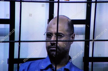 Saif Al-islam the Son of Former Libyan Leader Muammar Gaddafi is Seen on a Screen Broadcasting His Trial Taking Place in Zintan to Journalists at a Courtroom in Tripoli Libya 27 April 2014 Two Sons of Former Libyan Leader Gaddafi Are Facing Charges For Crimes Allegedly Committed in an Attempt to Abort the Uprising That Toppled Their Father Saadi and Saif Al-islam Gaddafi Are Among 37 Defendants Facing Charges That Include Incitement to Kill and Rape Opponents Enlisting Mercenaries and Embezzlement of Public Funds and Other Abuses During the 2011 Uprising That Led to the Ouster and Killing of Gaddafi Libyan Arab Jamahiriya Tripoli