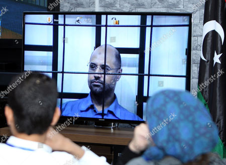 Journalists Watch Saif Al-islam the Son of Former Libyan Leader Muammar Gaddafi on a Screen Broadcasting His Trial Taking Place in Zintan to Journalists at a Courtroom in Tripoli Libya 27 April 2014 Two Sons of Former Libyan Leader Gaddafi Are Facing Charges For Crimes Allegedly Committed in an Attempt to Abort the Uprising That Toppled Their Father Saadi and Saif Al-islam Gaddafi Are Among 37 Defendants Facing Charges That Include Incitement to Kill and Rape Opponents Enlisting Mercenaries and Embezzlement of Public Funds and Other Abuses During the 2011 Uprising That Led to the Ouster and Killing of Gaddafi Libyan Arab Jamahiriya Tripoli