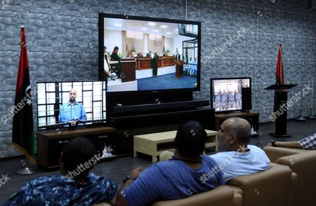 Stock Picture of Journalists Watch Saif Al-islam the Son of Former Libyan Leader Muammar Gaddafi on a Screen Broadcasting His Trial Along with Other Libyan Officials Under Former Libyan Leader Muammar Gaddafi Attend Their Trial at a Court in Tripoli Libya 22 June 2014 Two Sons of Former Libyan Leader Gaddafi Along with More Than 30 Gaddafi-era Officials Were Expected to Appear in Court Facing Charges For Crimes They Allegedly Committed While Trying to Stop the Uprising That Ousted Gaddafi the 37 Defendants Face Charges Varying From Murder Kidnapping and Embezzlement of Public Funds As Well As Abuses During the 2011 Uprising That Led to the Ouster and Killing of Gaddafi Libyan Arab Jamahiriya Tripoli