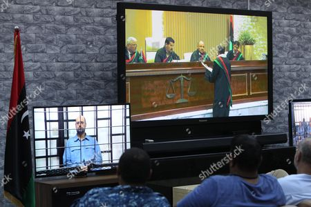 Journalists Watch Saif Al-islam (l) the Son of Former Libyan Leader Muammar Gaddafi on a Screen Broadcasting His Trial Along with Other Libyan Officials Under Former Libyan Leader Muammar Gaddafi Attend Their Trial at a Court in Tripoli Libya 22 June 2014 Two Sons of Former Libyan Leader Gaddafi Along with More Than 30 Gaddafi-era Officials Were Expected to Appear in Court Facing Charges For Crimes They Allegedly Committed While Trying to Stop the Uprising That Ousted Gaddafi the 37 Defendants Face Charges Varying From Murder Kidnapping and Embezzlement of Public Funds As Well As Abuses During the 2011 Uprising That Led to the Ouster and Killing of Gaddafi Epa/sabri Elmhedwi Libyan Arab Jamahiriya Tripoli