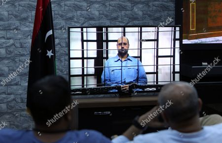 Journalists Watch Saif Al-islam the Son of Former Libyan Leader Muammar Gaddafi on a Screen Broadcasting His Trial Along with Other Libyan Officials Under Former Libyan Leader Muammar Gaddafi Attend Their Trial at a Court in Tripoli Libya 22 June 2014 Two Sons of Former Libyan Leader Gaddafi Along with More Than 30 Gaddafi-era Officials Were Expected to Appear in Court Facing Charges For Crimes They Allegedly Committed While Trying to Stop the Uprising That Ousted Gaddafi the 37 Defendants Face Charges Varying From Murder Kidnapping and Embezzlement of Public Funds As Well As Abuses During the 2011 Uprising That Led to the Ouster and Killing of Gaddafi Libyan Arab Jamahiriya Tripoli