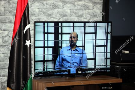 Journalists Watch Saif Al-islam the Son of Former Libyan Leader Muammar Gaddafi on a Screen Broadcasting His Trial Along with Other Libyan Officials Under Former Libyan Leader Muammar Gaddafi Attend Their Trial at a Court in Tripoli Libya 22 June 2014 Two Sons of Former Libyan Leader Gaddafi Along with More Than 30 Gaddafi-era Officials Were Expected to Appear in Court Facing Charges For Crimes They Allegedly Committed While Trying to Stop the Uprising That Ousted Gaddafi the 37 Defendants Face Charges Varying From Murder Kidnapping and Embezzlement of Public Funds As Well As Abuses During the 2011 Uprising That Led to the Ouster and Killing of Gaddafi Epa/sabri Elmhedwi Libyan Arab Jamahiriya Tripoli