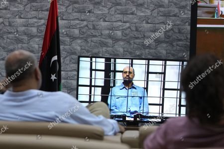 Stock Photo of Journalists Watch Saif Al-islam the Son of Former Libyan Leader Muammar Gaddafi on a Screen Broadcasting His Trial Along with Other Libyan Officials Under Former Libyan Leader Muammar Gaddafi Attend Their Trial at a Court in Tripoli Libya 22 June 2014 Two Sons of Former Libyan Leader Gaddafi Along with More Than 30 Gaddafi-era Officials Were Expected to Appear in Court Facing Charges For Crimes They Allegedly Committed While Trying to Stop the Uprising That Ousted Gaddafi the 37 Defendants Face Charges Varying From Murder Kidnapping and Embezzlement of Public Funds As Well As Abuses During the 2011 Uprising That Led to the Ouster and Killing of Gaddafi Epa/sabri Elmhedwi Libyan Arab Jamahiriya Tripoli