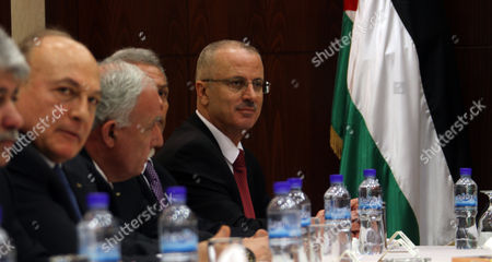 Palestinian Prime Minister Rami Hamdallah (r) and 24 Ministers Gather Around a Table After They Swore in During an Oath Ceremony in the West Bank City of Ramallah 06 June 2013 Hamdallah and 24 Ministers on 06 June Took the Oath Before Palestinian President Mahmoud Abbas After a Decision of Reshuffling the Government Abbas Chose the 54-year-old Academic For the Post After Salam Fayyad Resigned in April and Asked Him to Form a Government - Ramallah