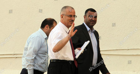 Palestinian Prime Minister Rami Hamdallah (c) Arrives to Attend the Oath Ceremony in the West Bank City of Ramallah 06 June 2013 Hamdallah and 24 Ministers on 06 June Took the Oath Before Palestinian President Mahmoud Abbas After a Decision of Reshuffling the Government Abbas Chose the 54-year-old Academic For the Post After Salam Fayyad Resigned in April and Asked Him to Form a Government - Ramallah