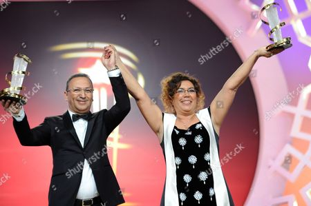 Stock Picture of Moroccan Film Producer Khadija Alami (r) and Zakaria Alaoui (l) Receive a Trophy in Tribut to Their Work During a Ceremony at the 14th Annual Marrakech International Film Festival in Marrakech Morocco 11 December 2014 the Festival Runs From 05 to 13 December Morocco Marrakech