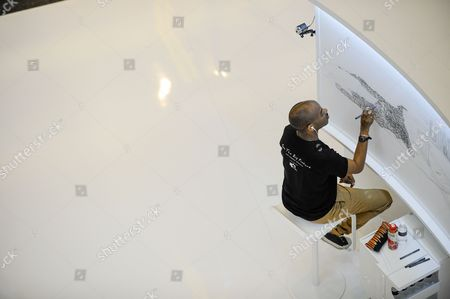 Stock Image of British Artist Stephen Wiltshire Sketches a Panorama of the Singapore Skyline at the Paragon Shopping Mall in Singapore 16 July 2014 Drawing Only From His Memory the Autistic Artist Has Completed Panoramas of Other Famous Cities Such As London New York and Rio De Janeiro the Finished Piece of Singapore Which Will Take Wiltshire Three Days to Complete Will Be Presented to President Tony Tan Keng Yam As a Gift For the 50th Anniversary of Singapore Singapore Singapore