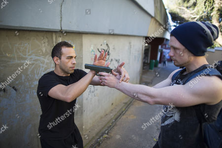 Stock Picture of Tactical Kung Fu Training (tkt) Instructor Elan Lea From Los Angeles Usa (l) Practices a Gun Take Down Technique in an Alleyway Outside the Chinese Martial Arts and Health Centre in Cape Town South Africa 17 September 2014 Tkt is a Self-defense System Developed For Modern Day Close Quarter Real Life Situations Developed From Traditional Chinese Martial Arts It Condenses That Knowledge to Guide Students Through a Practical Curriculum of Techniques Application and Psychology Covering Gun Knife and Unarmed Situations As Well As Teaching Situational Awareness and Avoidance South Africa Has One of the Highest Violent Crime Rates in the World with Muggings Attacks and Rape a Daily Occurence South Africa Cape Town