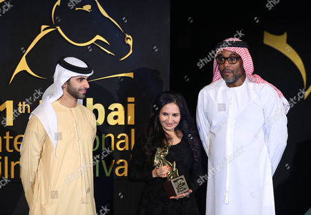 Attended by Us Director Lee Daniels (r) Yemeni Film Producer Khadija Al-salami (c) Receives From Sheikh Mansour Bin Mohammed Bin Rashid Al Maktoum (l) the Award For Best Fiction Film 'Ana Nojoom Bent Alasherah Wamotalagah' (i Am Nojoom Age 10 and Divorced) During the Muhr Awards Ceremony of the 11th Dubai International Film Festival (diff) 2014 in Gulf Emirate of Dubai United Arab Emirates 16 December 2014 the Diff Runs From 10 to 17 December United Arab Emirates Dubai