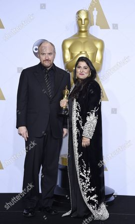 Stock Image of Sharmeen Obaid-chinoy (r) Holds the Oscar For Best Documentary Short Subject For 'A Girl in the River: the Price of Forgiveness' As She Stands with Presenter Louis C K (l) During the 88th Annual Academy Awards Ceremony at the Dolby Theatre in Hollywood California Usa 28 February 2016 United States Hollywood
