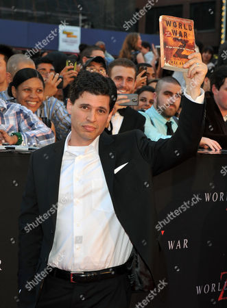 Us Author Max Brooks Holds Up His Book World War Z As He Arrives on the Red Carpet For the New York Movie Premiere of 'World War Z' in Times Square in New York Usa 17 June 2013 United States New York