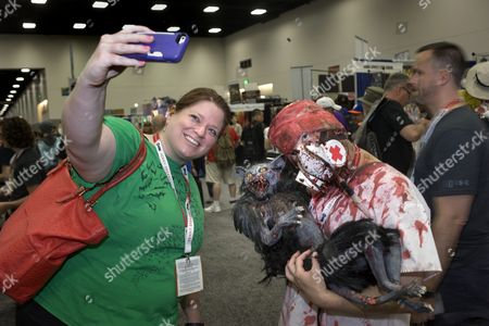 Stock Picture of Liz Schulte From Missouri (l) Takes a Photograph of Herself with Mike Erwin who is Holding a Puppet Cat From the Movie Reanimator on the Second Day of Comic-con 2015 in San Diego California Usa on 10 July 2015 United States San Diego