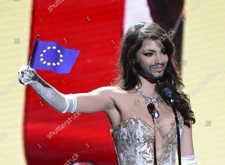 Stock Photo of Miss Austria Amina Dagi Sports a Mustache and Beard Reminding of Austria's Eurovision Song Contest Winner Conchita Wurst As She Waves the European Union Flag As She Competes in National Costume Contest During Filming For the 2016 Miss Universe Pageant at the Planet Hollywood Hotel & Casino in Las Vegas Nevada Usa 16 December 2015 the Miss Universe Pageant Will Take Place on 20 December 2015 United States Las Vegas