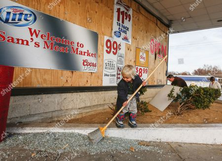 Zeke Davis-isgrig (l) Sweeps Up Broken Glass As He Helps John Powell (c) and Leah Bailey (r) Clean Up Damage Around Sam's Meat Market in Ferguson Missouri Usa 28 November 2014 Relative Calm Has Returned to the Area Following a Night of Property Burning Shooting and Mayhem Followed by Two Nights of Protests Protestors Took to the Streets in Anger That Ferguson Police Officer Darren Wilson was not Indicted by a Grand Jury For the Shooting Death of Teenager Michael Brown in August 2014 United States Ferguson