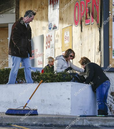 John Powell (l) Zach Davis-isgrig (2-l) Leah Bailey (2-r) and Emily Davis Clean Up Broken Glass Around Sam';s Meat Market in Ferguson Missouri Usa 28 November 2014 Relative Calm Has Returned to the Area Following a Night of Property Burning Shooting and Mayhem Followed by Two Nights of Protests Protestors Took to the Streets in Anger That Ferguson Police Officer Darren Wilson was not Indicted by a Grand Jury For the Shooting Death of Teenager Michael Brown in August 2014 United States Ferguson