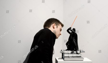 Stock Image of A Man Looks at a Darth Vader Figurine Which is Expected to Sell For 200-400 Us Dollars During a Preview of an Auction of Items Associated with the Star Wars Films at Sotheby's in New York New York Usa 02 December 2015 the Auction Which is Being Held Online on 11 December Features a Number of Rare and Valuable Star Wars Collectables Which Are All From the Collection of the Japanese Designer Nigo United States New York