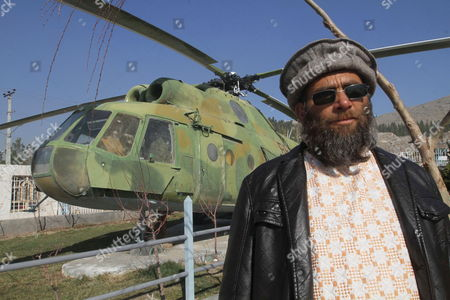 Abdullah a Russian Soldier who Had Been Arrested by Mujahedin at Time of Russian Invasion of Afghanistan Poses For a Photograph Next to an Abandoned Russian Military Helicopter As He Works at the Only War Museum Remembering Victims of the War in Herat Afghanistan 15 February 2014 in 1989 the Last Soviet Troops Under the Command of General Boris Gromov Crossed the Amu Darya River Separating Afghanistan From Uzbekistan Afghanistan Herat