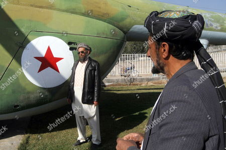 Abdullah (l) a Russian Soldier who Had Been Arrested by Mujahedin at Time of Russian Invasion of Afghanistan Poses For a Photograph Next to an Abandoned Russian Military Helicopter As He Works at the Only War Museum Remembering Victims of the War in Herat Afghanistan 15 February 2014 in 1989 the Last Soviet Troops Under the Command of General Boris Gromov Crossed the Amu Darya River Separating Afghanistan From Uzbekistan Afghanistan Herat