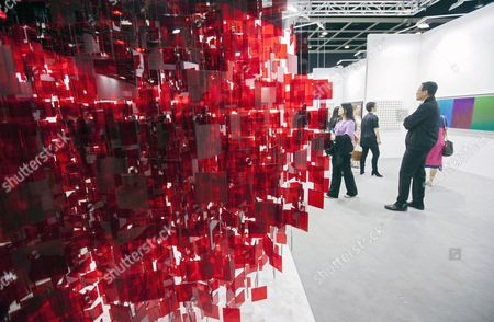 People Walk Past an Artwork by Argentinian Artist Julio Le Parc Entitled 'Sphere Rouge' at Art Basel 2014 Hong Kong China 14 May 2014 Art Basel is in Its Second Year in Hong Kong and Features 245 Galleries From 39 Countries Hong Kong is the Third Largest Art Market in the World by Auction Revenue the Show Runs From 15 to 18 May China Hong Kong