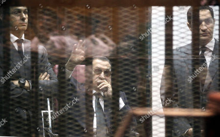 Former Egyptian President Hosni Mubarak (c) Flanked by His Sons Gamal Mubarak (l) and Brother Alaa Mubarak (r) Waves From the Defendants' Cage During Their Trial at the Police Academy in Cairo Egypt 09 May 2015 According to Local Reports an Egyptian Court Sentenced Mubarak to Three Years in Prison in a Retrial on Charges of Corruption Handing Down the Same Sentence to His Sons Alaa and Gamal and Ordering All Three to Pay a Fine of 125 Million Egyptian Pounds (16 4 Million Dollars) Egypt Cairo
