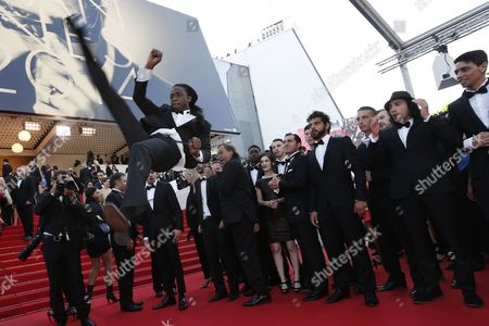 A Break Dancer Performs on the Red Carpet As French Director Tony Gatlif (back C) Arrives For the Screening of 'Deux Jours Une Nuit' (two Days One Night) During the 67th Annual Cannes Film Festival in Cannes France 20 May 2014 the Movie is Presented in the Official Competition of the Festival Which Runs From 14 to 25 May France Cannes