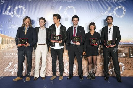 Stock Picture of From (l-r): the Winners of the 40th Edition of the Deauville American Film Festival Us Film Director Saar Klein Us Composer Nicholas Britell Us Actor Miles Teller Us Film Director Damien Chazelle Us-iranian Director Lily Amirpour and Us Director David Robert Mitchel Pose with Their Trophies During the Photocall of the Winners Following the Closing Ceremony of the 40th Annual Deauville American Film Festival in Deauville France 13 September 2014 France Deauville
