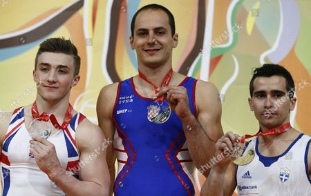 Croatian Gymnast Marijo Moznik Celebrates His Gold Medal Victory on the Podium (c) with British Gymnast Sam Oldham Taking Second Place Silver Medal (l) and Greek Gymnast Vlasios Maras Taking Third Place Bronze Medal After the Horizontal Bar Competition During the Men's Apparatus Final at the European Artistic Gymnastic Championships in Montpellier France 19 April 2015 France Montpellier