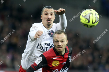 Zlatan Ibrahimovic (l) of Psg Vies For the Ball Against Lars Jacobsen (front) of Ea Guingamp During the French Ligue 1 Soccer Match Between Ea Guingamp and Psg at the Roudourou Stadium in Guingamp France 14 December 2014 France Guingamp