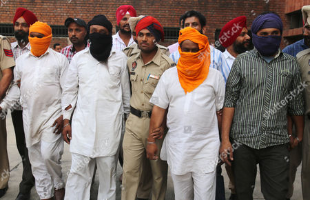 Officers of the State Special Operation Cell (ssoc) Punjab and Punjab Police Personnel Parade 4 Alleged Smugglers (in Random Order-faces Covered) Allegedly Having Links with Pakistani Smugglers who Were Caught with 24 Kg Heroin in Amritsar India 28 October 2013 Four Alleged Smugglers Namely Jasbir Singh Kuldip Singh Avtar Singh and Tarsem Singh Were Apprehended Near Amritsar when They Were Bringing the Consignment From Fazilka Sector on 27 October According to a Press Release India Amritsar