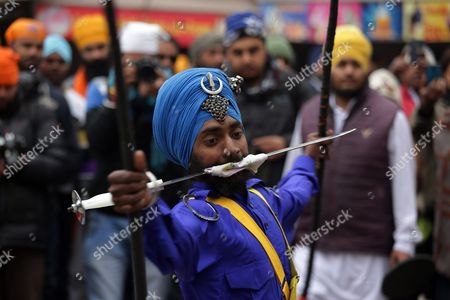 A Sikh Man Holds a Sword Partially Covered with a Cloth in His Mouth to Exhibit His Skills As He Performs the Gatka a Form of Sikh Martial Art During a Religious Procession on the Eve of the 351st Birth Anniversary of the Tenth Guru Or Master of the Sikhs Sri Guru Gobind Singh in Amritsar India 15 January 2016 Guru Gobind Singh Ji was the Tenth Sikh Guru who Initiated the Special Order Or Sect of the Sikhs Called the Khalsa Panth India Amritsar