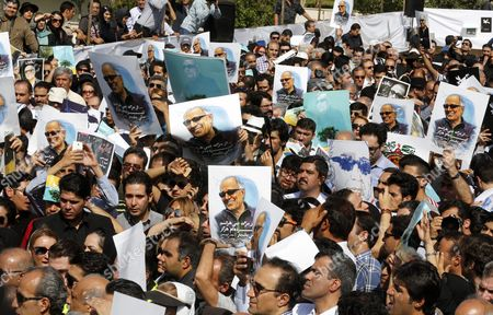 Stock Image of Iranians Hold Posters Depicting Iranian Film Director Abbas Kiarostami During a Funeral Ceremony at the Center For the Intellectual Development of Children and Young Adults in Tehran Iran 10 July 2016 According to Media Reports Award-winning Filmmaker Kiarostami Died After Several Months of Illness at the Age of 76 in Paris France on 04 July 2016 He Had Been Suffering From Gastrointestinal Cancer Since the End of March and Had Been Undergoing Hospital Treatment in France Kiarostami Whose Career Spanned 40 Decades was Considered One of the Most Prominent Directors of Iran Iran (islamic Republic Of) Tehran