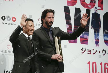 Canadian Actor/cast Member Keanu Reeves (r) Waves to Fans with Three-time Olympic Judo Champion in Men's 66 Kg Category Tadahiro Nomura (l) As He Receives a Judo's Kuro-obi Or Black Belt by Nomura During the Premiere of 'John Wick' Directed by Chad Stahelski and David Leitch in Tokyo Japan 30 September 2015 the Movie Will Be Released in Japan Theaters on 16 October 2015 Japan Tokyo