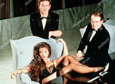'Head Office'  Film - 1985 -     Jane Caldwell (Jane Seymour) sits in an armchair with her legs up on an office desk, she wears stockings and underwear, Jack Issel (Judge Reinhold) leans on the back of the chair and Inc Chairman Pete Helmes (Eddie Albert) leans on the desk. the two men are dressed in tuxedo's.