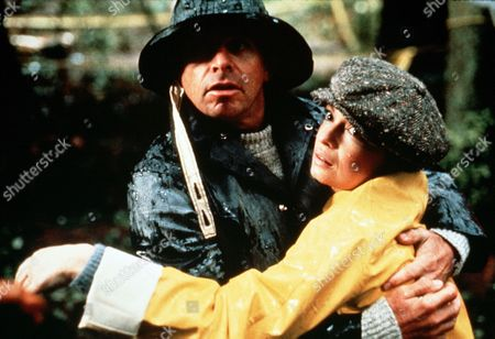 "'Jane Doe'  TV Film - 1983 -   Victoria  Schaffer ""Jane Doe"" (Karen Valentine) is held by Detective Quinn (William Devane), both are hats and coats to protect them from the rain."