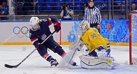Stock Picture of Jocelyne Lamoureux (l) of Usa Takes the Puck in Against Goalkeeper Kim Martin Hasson (r) of Sweden During the Semi Final Match Between Usa and Sweden at the Shayba Arena in the Women's Ice Hockey Tournament at the Sochi 2014 Olympic Games Sochi Russia 17 February 2014 Russian Federation Sochi