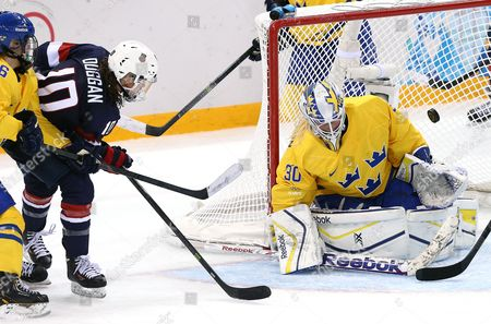 Meghan Duggan (l) of Usa in Action Against Kim Martin Hasson (r) the Goalkeeper of Sweden During Their Semi Final Match Between Usa and Sweden at the Shayba Arena in the Women's Ice Hockey Tournament at the Sochi 2014 Olympic Games Sochi Russia 17 February 2014 Russian Federation Sochi