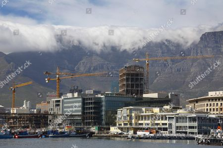 Construction Cranes Are Seen Behind the I&j Fishing Fleet Headquarters at the Victoria and Alfred Waterfront (v&a) in Cape Town South Africa 02 February 2016 in December 2015 the V&a Waterfront Announced a 700 Million Rand Canal District the First Phase of the New District is Under Construction with a Corporate Head Office For British American Tobacco South Africa (bat South Africa) As the Initial Project in the Mixed Use Area Totalling 75 000 Square Meters the Mixed Use Canal District Straddles Both Sides of Dock Road South Africa Cape Town
