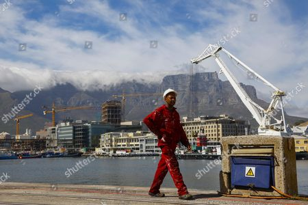 Construction Cranes Are Seen Behind a Dockyard Worker Walking Along a Quay at the Victoria and Alfred Waterfront (v&a) in Cape Town South Africa 02 February 2016 in December 2015 the V&a Waterfront Announced a 700 Million Rand Canal District the First Phase of the New District is Under Construction with a Corporate Head Office For British American Tobacco South Africa (bat South Africa) As the Initial Project in the Mixed Use Area Totalling 75 000 Square Meters the Mixed Use Canal District Straddles Both Sides of Dock Road South Africa Cape Town