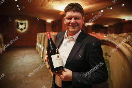 Stock Image of A Photograph Made Available 15 October 2015 Shows Ceo of La Motte Hein Koegelenberg Poses For a Portrait with a Bottle of One of His Presidential Series Named After Former South African President Fw De Klerk in a Cellar at La Motte Wine Farm in Franschoek South Africa 14 October 2015 Koegelenberg is South Africa's Leading Exporter of South African Wines to China South Africas Wine Sales to China Grew by 63 Percent in 2014 the Current Ceo of La Motte Hein Koegelenberg Has Said the La Motte Brand Sold More Wine in China in 2015 Than in 2014 Koegelenberg Expects Chinas Demand For South African Wine Will Plateau at About 10-million Bottles For Some Time Situated in the Beautiful Franschhoek Valley in South Africas Cape Winelands La Motte is Home to Internationally Recognised Wines in 1695 a Piece of Land in the Franschhoek Valley was Granted to German Immigrant Hans Hattingh in 1709 the Land was Purchased by French Huguenot Pierre Joubert who is Believed to Have Named It After the Village of His Birth in Provence La Motte Daigues Viticulture on La Motte was Established in 1752 with the Planting of 4 000 Vines by Huguenot Descendant Gabri?l Du Toit South Africa Franschoek