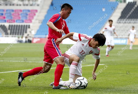 Stock Photo of China's Xie Pengfei (r) Fights For the Ball with North Korea's Sim Hyon-jin (l) During the Men's Group F Soccer Qualifier Match Between China and North Korea at the 17the Asian Games in Incheon South Korea 15 September 2014 Korea, Republic of Incheon
