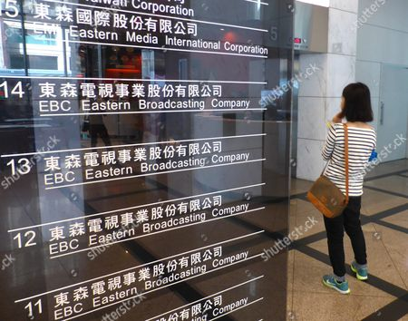 A Woman Waits For the Elevator Next to a Signboard Showing the Name of the Eastern Broadcasting Corp (ebc) in a Buidling in Taipei Taiwan 23 November 2015 on 23 November Taiwan Said It Would Block Us Firm Dmg Entertainment's Buying Stake in Ebc if the Stake is Over 50 Per Cent and if Dmg is Linked with China's Military a Day Earlier Dmg Ceo Dan Mintz Told the Los Angeles Times That He Had Agreed to Buy 61 Per Cent of Carlyle Group's Stake in Ebc For Us$600 Million So As to Boost Airing of Dmg's Chinese Content Programmes the News Triggered Strong Reaction From the Opposition Democratic Progressive Party Saying It was Firmly Opposed to the Sale Fearing China's Control of Taiwan Media and Encroachment on Freedom of Speech Ebc Called Dongsen Tv in Chinese Has Several Channels Broadcasting News and Entertainment Programmes in Taiwan Southeast Asia and the Us Taiwan Taipei
